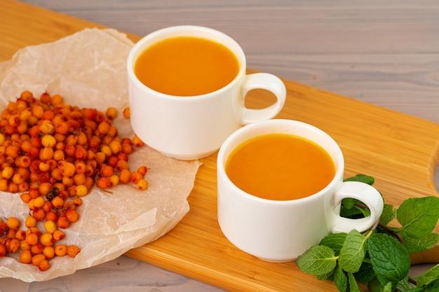 Thé à l'argousier servi sur une table en bois close up