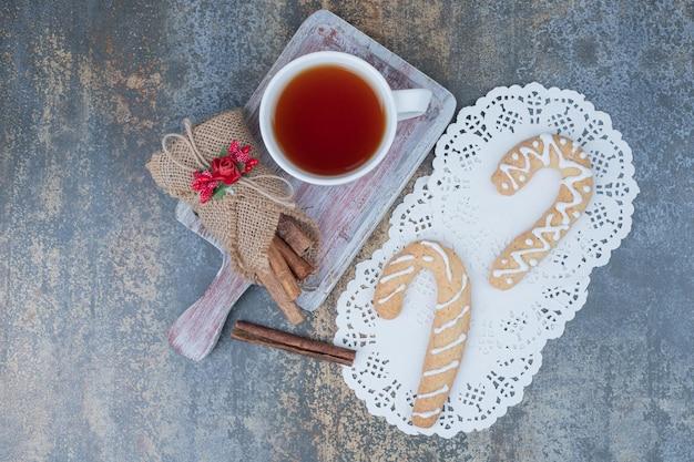 Thé aromatique dans une tasse blanche avec des bâtons de cannelle et un biscuit de noël sur une table en marbre.