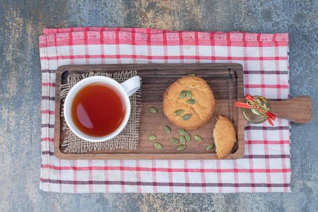 Thé aromatique dans une tasse blanche avec des biscuits et des graines de citrouille sur table en marbre
