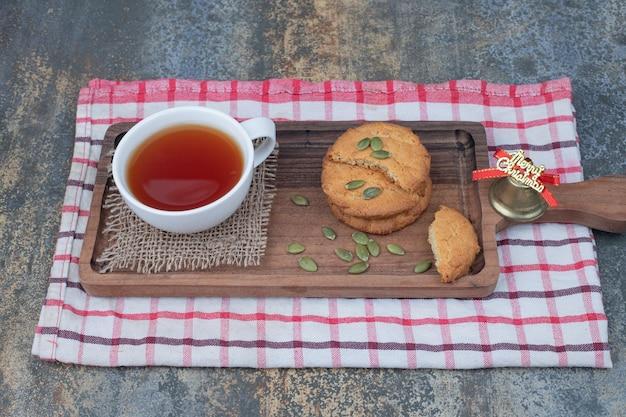 Thé aromatique dans une tasse blanche avec des biscuits et des graines de citrouille sur une table en marbre