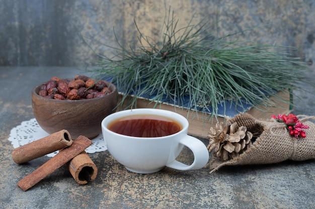 Thé aromatique dans une tasse blanche avec cannelle et pomme de pin sur table en marbre