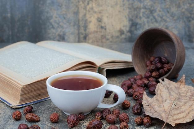 Thé aromatique dans une tasse blanche avec feuille et livre sur table en marbre