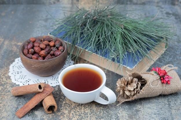 Thé aromatique en tasse blanche avec cannelle et pomme de pin sur table en marbre