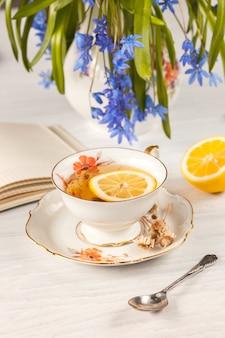 Thé au citron et bouquet de primevères bleues sur la table