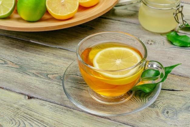 Thé au citron avec citron et citron vert sur une table en bois