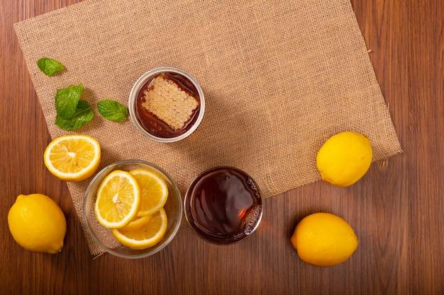 Thé au citron avec des feuilles de menthe et du miel mélangé des boissons fraîches dans le verre