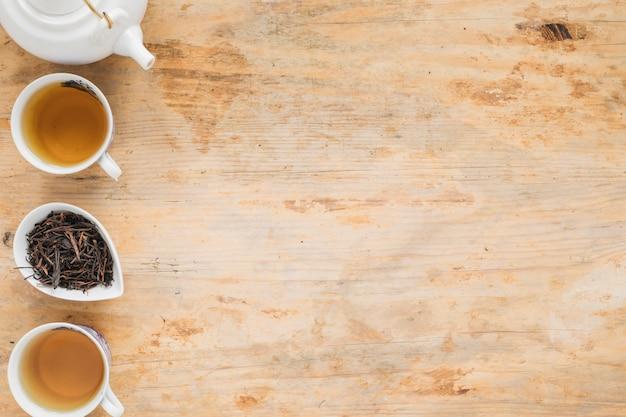 Thé au citron avec des feuilles de thé sèches et théière sur une table en bois