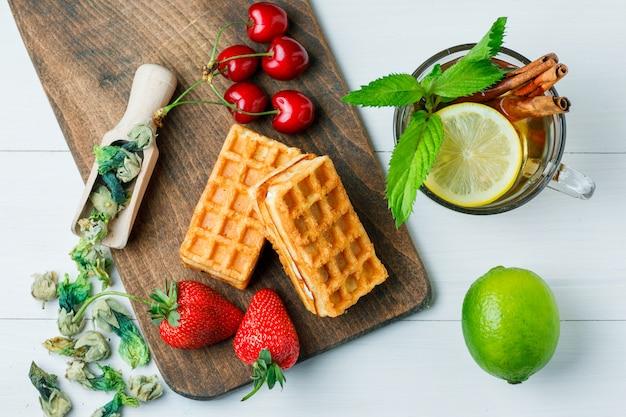 Thé au citron, gaufre, herbes séchées, fruits, menthe, cannelle dans une tasse sur une planche à découper en bois et à plat.