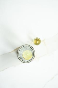 Thé au citron glacé avec du sucre liquide sur une surface blanche