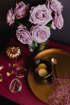 Thé au citron sur un plateau en laiton près du vase à fleurs