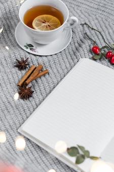 Thé au citron près de cahier sur plaid tricoté