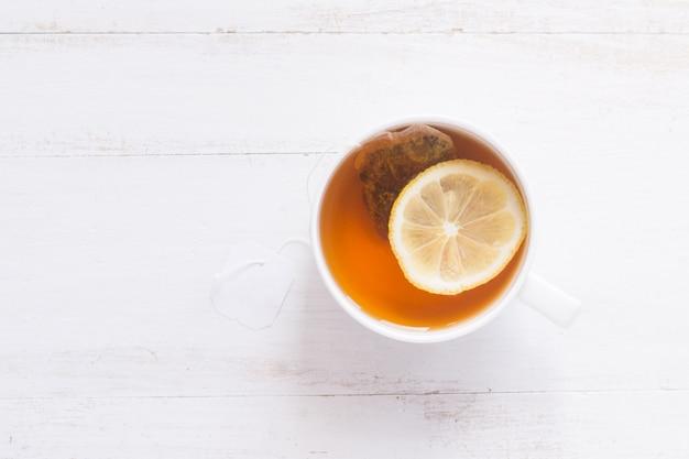 Thé au citron sur une table en bois blanche