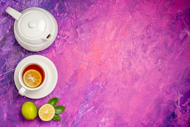 Thé au citron une tasse de thé au citron à côté de la théière et des citrons verts sur le côté gauche de la table rose-violet