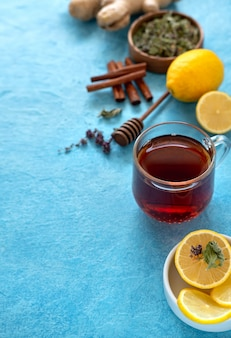 Thé au gingembre au citron dans une tasse en verre à la surface bleue