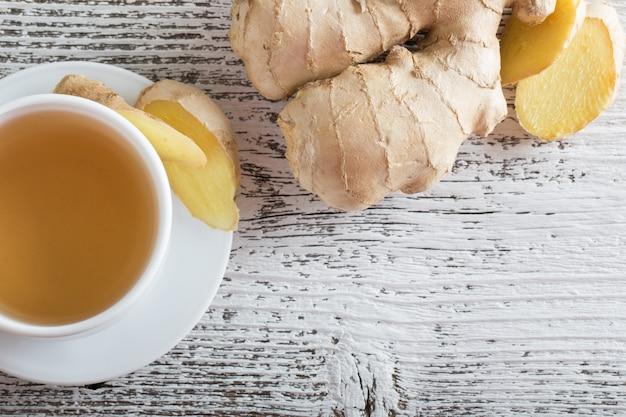 Thé au gingembre dans une tasse blanche sur fond de bois
