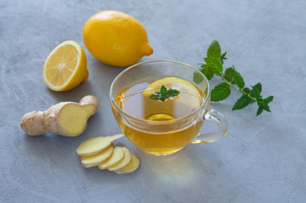 Thé au gingembre dans une tasse en verre avec du citron et de la menthe sur table en pierre