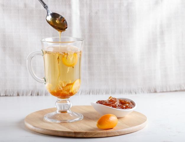 Thé au jasmin avec kumquat dans une coupe en verre et une cuillère avec de la confiture, sur une planche de bois posée sur une table blanche.