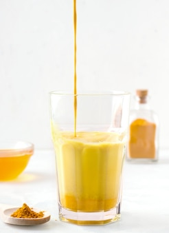 Thé au lait au curcuma sur fond blanc