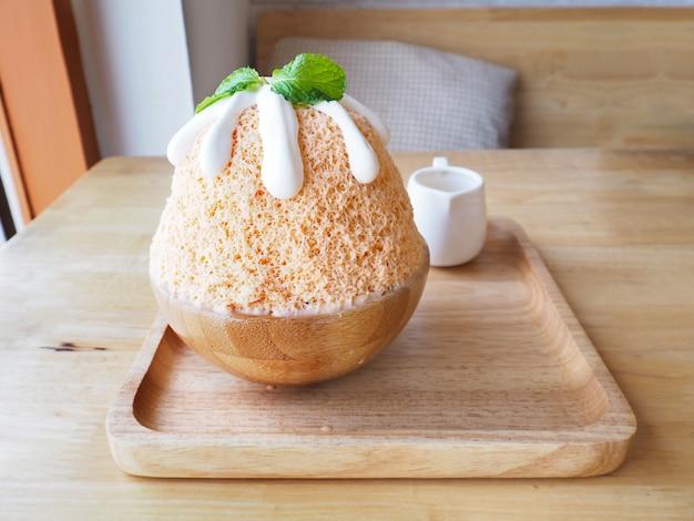Thé au lait bingsu (dessert coréen) sur une plaque en bois.
