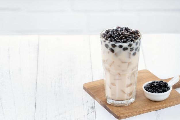 Thé au lait à bulles avec garniture de perles de tapioca, célèbre boisson taïwanaise sur fond de table en bois blanc dans un verre à boire, close up, copy space