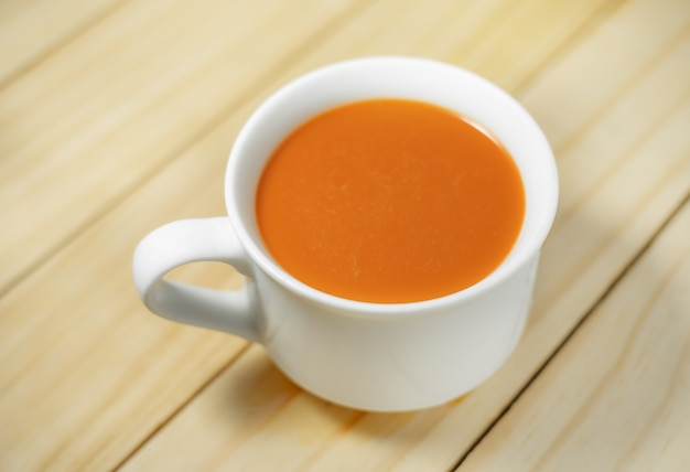 Thé au lait chaud dans une tasse blanche en bois