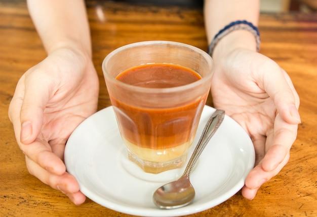 Thé au lait chaud dans une tasse sur la table en bois