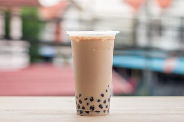Thé au lait de glace avec bulle boba dans le verre en plastique sur le motif de bois