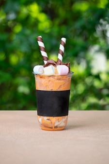 Thé au lait glace pilée sur table en bois au café