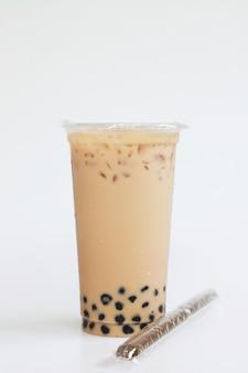 Thé au lait glacé style taiwan grande tasse en plastique avec mise près sur fond blanc, concept de boisson sucrée fraîche et fraîche, nourriture et boisson