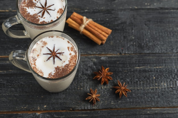 Thé au lait maison à la cannelle et l'anis sur fond noir rustique en bois dans une tasse en verre