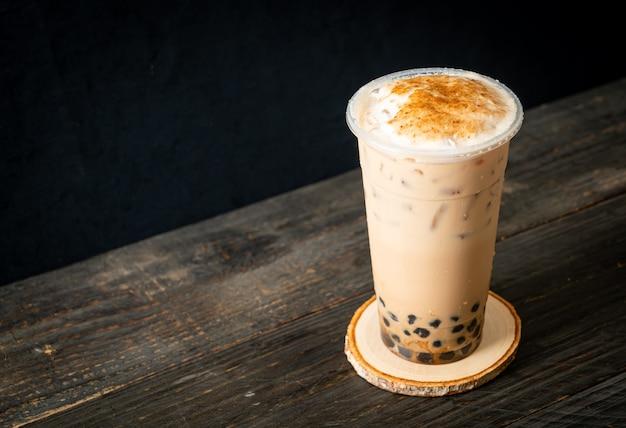 Thé au lait de taiwan avec bulle et fromage brûlé sur table en bois