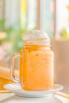 Thé au lait thaïlandais garni de crème fouettée dans une tasse en bocal avec poignée.