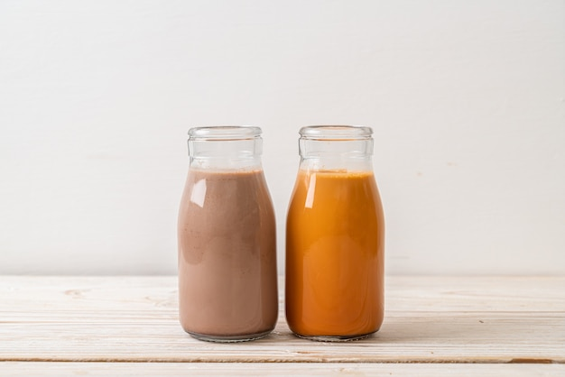 Thé au lait thaïlandais et lait au chocolat en bouteille sur la surface du bois