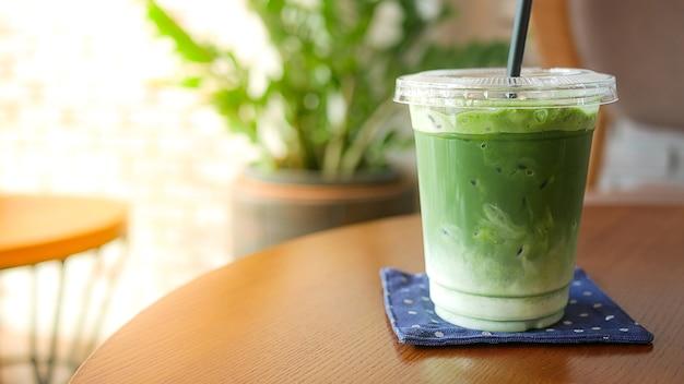Thé au lait vert matcha glacé sur une table en bois.