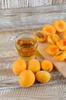 Thé aux abricots dans une tasse en verre sur planche de bois et à découper, gros plan.