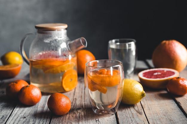 Thé aux agrumes dans une théière transparente sur une table avec du pamplemousse et sur une table en bois