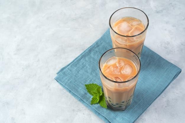 Thé aux bulles de lait avec des perles de tapioca sur un mur gris. vue horizontale, copiez l'espace.