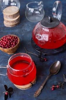 Thé aux canneberges chaud dans une tasse en verre et une théière sur un fond sombre et froid.