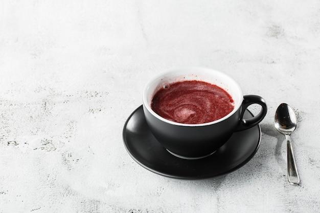 Thé aux canneberges, rouge ou framboise dans une tasse sombre isolé sur fond de marbre brillant. vue aérienne, espace copie. publicité pour le menu du café. menu du café. photo horizontale.