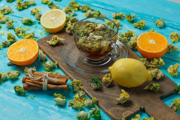 Thé aux épices, orange, citron, herbes séchées dans une tasse sur bleu et planche à découper, vue grand angle.
