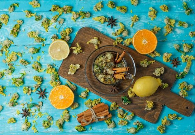 Thé aux épices, orange, citron, herbes séchées dans une tasse sur planche bleue et à découper, vue de dessus.