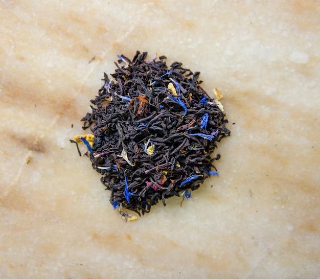 Thé aux feuilles noires aux pétales de fleurs bleues.