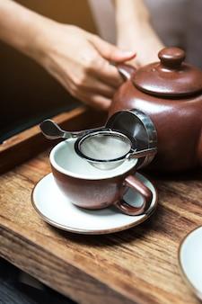 Thé aux fleurs chaudes servi en versant de la tasse à travers l'infuseur à passoire à thé en acier inoxydable dans une tasse en porcelaine brune.