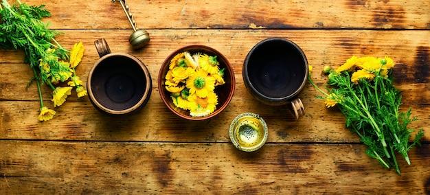 Thé aux fleurs de guérison. théière avec thé aux fleurs de chrysanthème. phytothérapie. thé aux herbes.