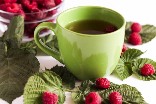 Thé aux framboises d'été dans une tasse verte