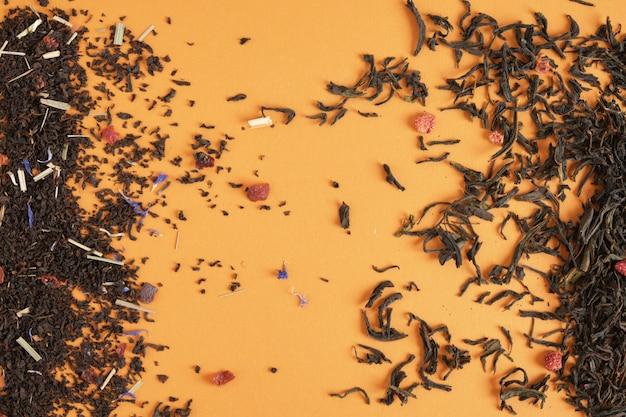 Thé aux fruits et aux baies éparpillés sur la texture du thé de fond marron