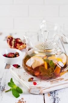 Thé aux fruits avec baies, citron, citron vert et feuilles de menthe dans une théière en verre sur fond de bois clair blanc. mise au point sélective.