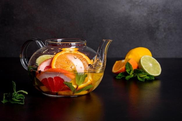 Thé aux fruits chaud avec citron, menthe, orange, citron vert et pamplemousse dans une belle théière en verre