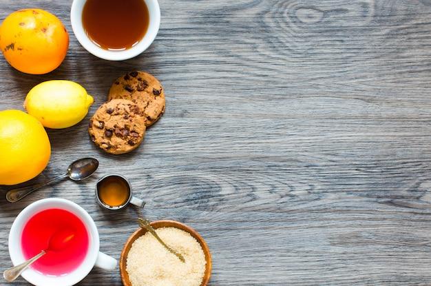 Thé aux fruits avec citron, lait, miel, orange, grenade, sur un fond en bois