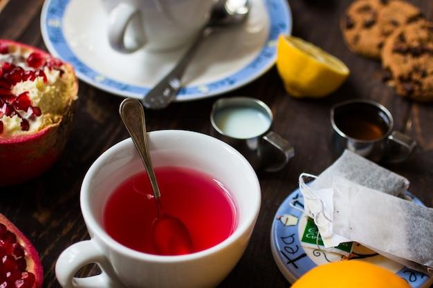Thé aux fruits avec citron, lait, miel, orange, grenade, sur une surface en bois